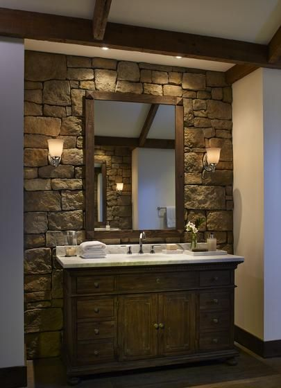 stone wall behind bathroom vanity, dark wood cabinet, marble countertop, sconces, dark wood ...