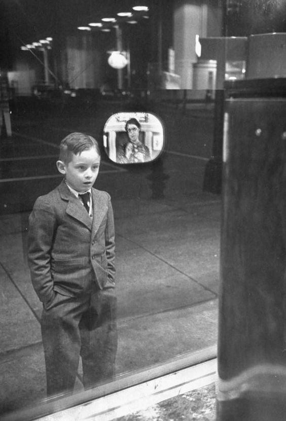 A boy watching TV for the first time in an appliance store window, 1948.: