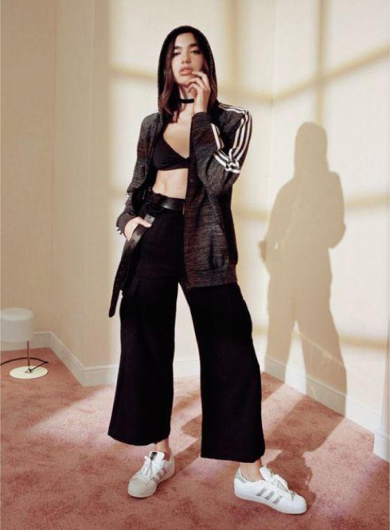 O estilo de Dua Lipa. Moletom esportivo com ziper cinza, top preto, calça pantacourt preta, tênis banco adidas