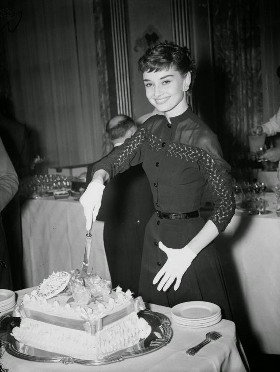 Одри Хепберн позирует с тортом во время коктейльной вечеринки в ее честь. 1953 г