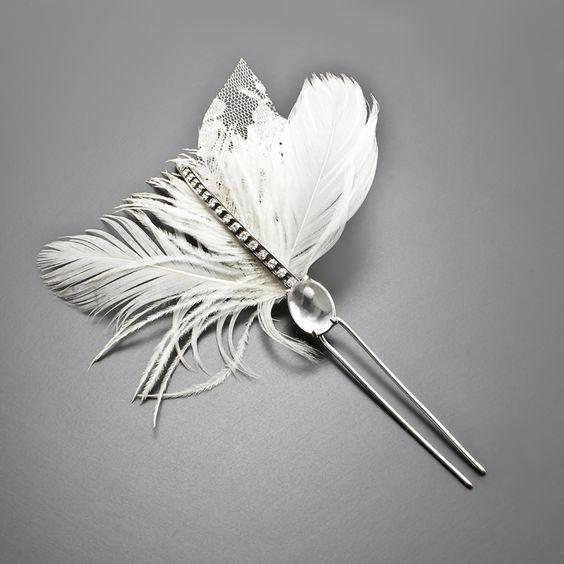 Grampo Adriana de prata com quartzo cristal adornado por belíssimas plumas, penas e folhas de renda e para arrematar um detalhe de strass Swarovski. Simplesmente perfeito! R$540,00.