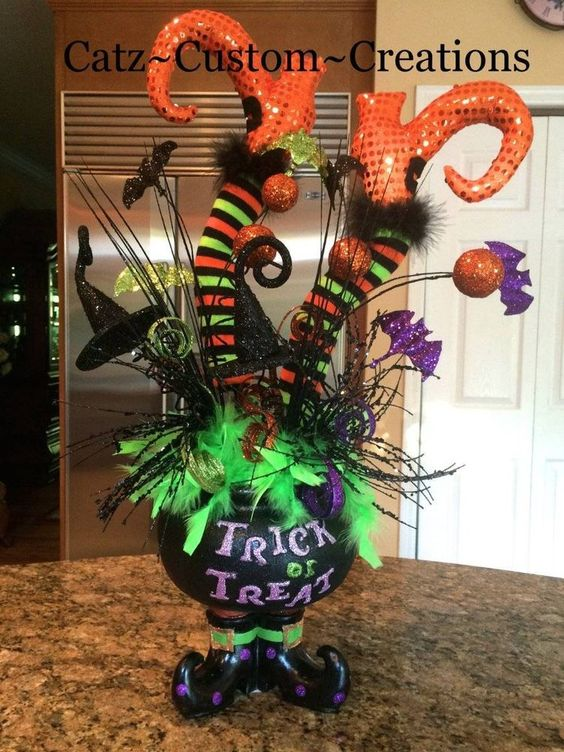 Halloween centerpieces witch legs and feather boas on