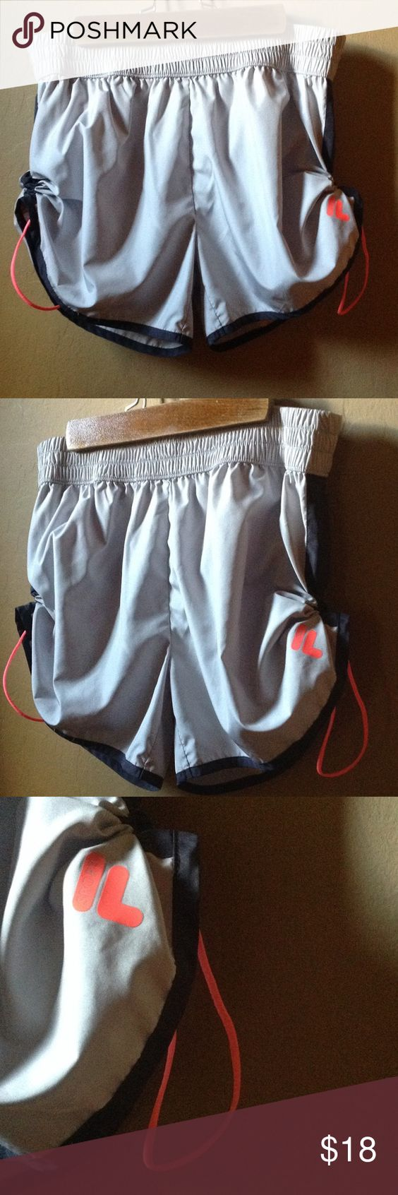 FILA Sport Activewear Shorts Light gray with hot pink trim. These shorts are super cool! They have a bungee drawstring on each side of the shorts that can be adjusted. You can scrunch them up to be very high or let them go all the way down for a regular short look. They have built in undergarments. Fila Shorts
