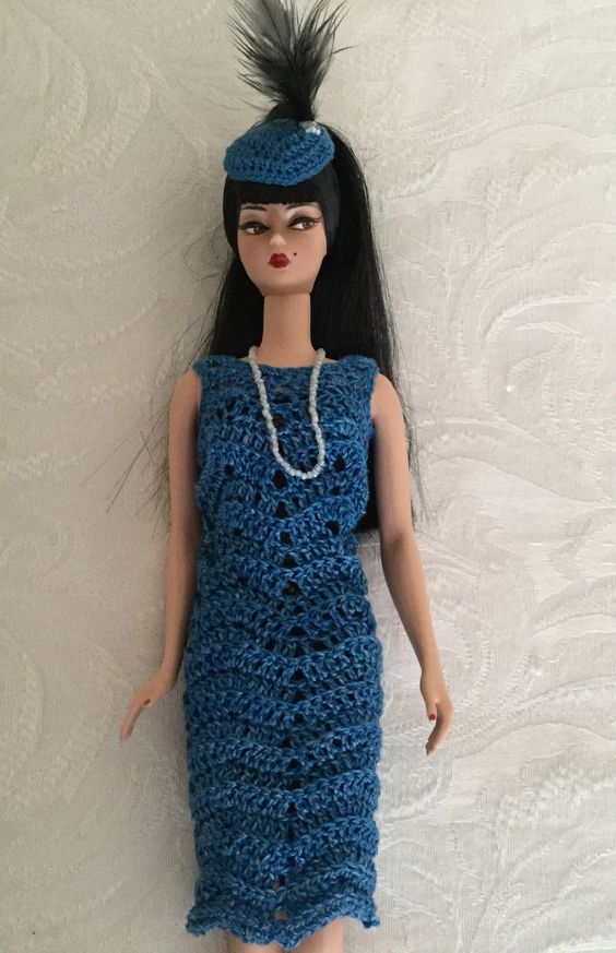Blue flapper dress for Silkstone Barbie, with bead necklace, and hat with feather and beading.  Dress pattern adapted from dress pattern at https://sites.google.com/site/hazel3crochets/zig-zag-short-dress   KDS Fashion for Barbie and Friends