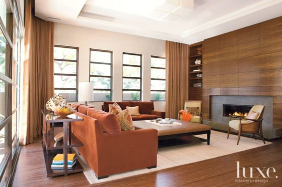 Contemporary armchairs with a midcentury feel flank the Mozambique wood-encased fireplace in the living room, while floor-to-ceiling draperies add comfort.