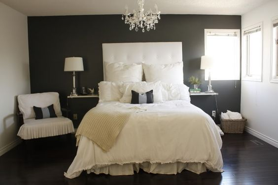 Dark grey accent wall dark floors white ceiling and moldings crystal chandelier white Master bedroom grey floor