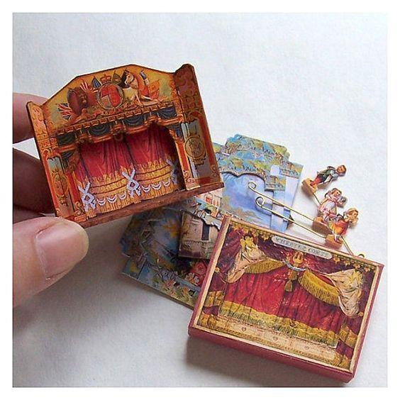 Este teatro miniatura viene completo con una cortina, 5 piezas de escenarios y 3 personajes para El jardín de hadas. Es un teatro de funcionamiento y puede organizar y reorganizar las piezas como usted por favor.  También es una caja hecha a mano, para almacenar la escenografía y los personajes cuando no esté en uso.  El teatro se construye de la madera. La caja, escenario y personajes se hacen de papel y tarjeta libre de ácido. Los personajes están montados en madera y tienen metal sliders…