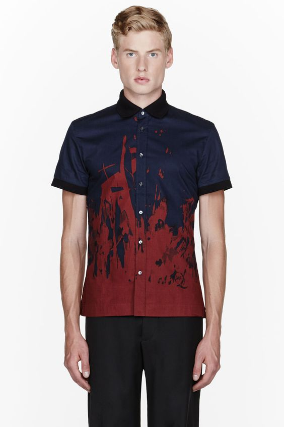 MCQ ALEXANDER MCQUEEN //  Navy paint-splattered short sleeve shirt  32114M040004  Short sleeve shirt in navy blue. Contrasting ribbed spread collar and sleeve cuffs in black. Button closure at front. Paint splatter effect dyed throughout lower portion in red. Logo print at front hem. Tonal stitching. 100% cotton. Machine wash warm. Imported.  $385 CAD