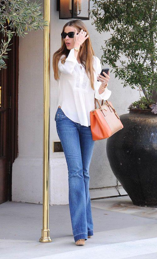 SOFÍA VERGARA Fiel a su característico look de jeans acampanados, top holgado, altísimas sandalias de tacón de cuña, gafas de sol y bolso d...: