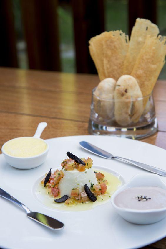 Pães variados, panacotta de palmito pupunha com cubinhos de tomate e alho negro, pastinha de cream cheese com jabuticaba e manteiga com flor de sal