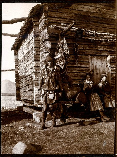 A man and two women in front of a traditional Sami notched log store house (stabbur) in timber. Tromso, Norway. En mann og to kvinner ved la...