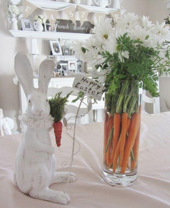 Strauß aus weißen Chrysanthemen unf Vasenfüllung aus Möhren in runder Bodenvase