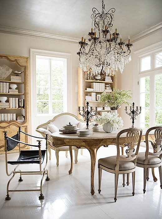 French Country interior design and dining room decor inspiration for decorating with antiques! Tara found a boiserie (sculptured paneling) in a house near Versailles and repurposed it as a bookcase in her dining room. The bench and the candelabras (based on a pair Tara found in Lyon) come from Tara Shaw Maison. A midcentury chair ensures the room doesn't feel dated. #francophile #interiordesignideas #interiordesigner #diningroomdecor #diningroomideas #luxuryhomes #antiques #crystalchandelier #decoratingideas #French