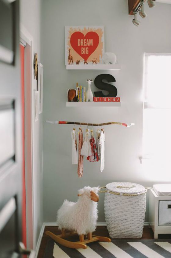 Perfectly styled shelves with branch to display baby clothes! #nursery
