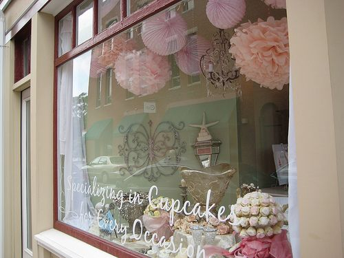 I love the pompoms and chandelier hanging from the ceiling of this window display...