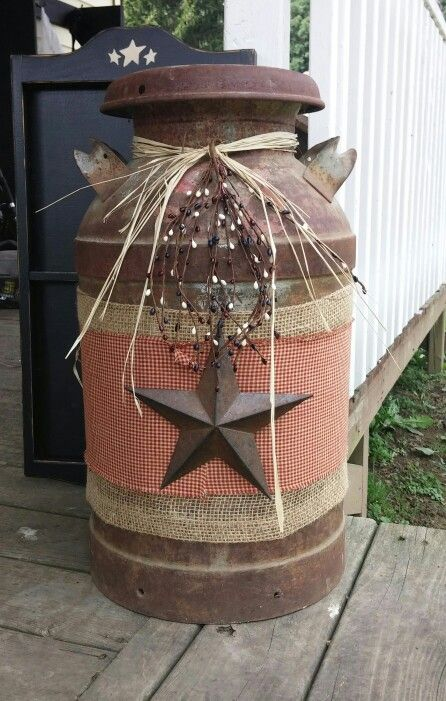 Old milk can just some burlap ginham fabric raffia and pip berries. Attached burlap and fabric with spay adhesive.