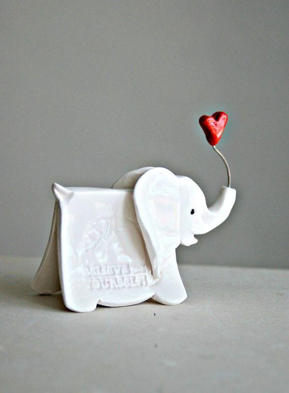 Petit éléphant sculpture avec des mots imprimés de sagesse et tenant un coeur dans son coffre.