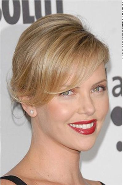 Charlize has gone for a clean and classy updo hairstyle. Her long locks have all been gathered together and styled back, leaving her with this incredibly chic and stylish look. Bangs are laid out across her forehead which adds to the look.This haircut is long with long bangs.This hair colour is a light brown with light blonde highlights.