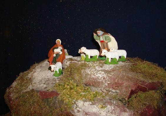 Sur le sommet de la montagne un couple de berger, le berger tient son chapeau, le vent souffle fort, il a du mal à avancer, son épouse tient un agneau fatigué par une longue marche.