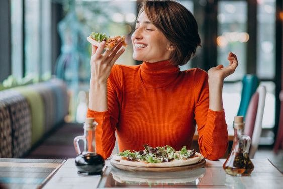 Young pretty woman eating pizza at pizza... | Free Photo #Freepik #freephoto #food #people #love #family