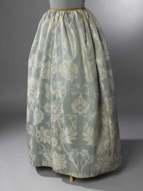 Rok van wol, lichtgroen met grote witte bloem en zoom en splitten afgezet met koord | Modemuze