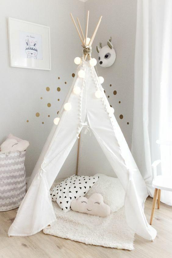 guirlande lumineuse boule blanche sur la partie supérieure d'un tipi indien en tissu blanc, chambre d'enfant cocoon en couleurs claires, blanc et beige