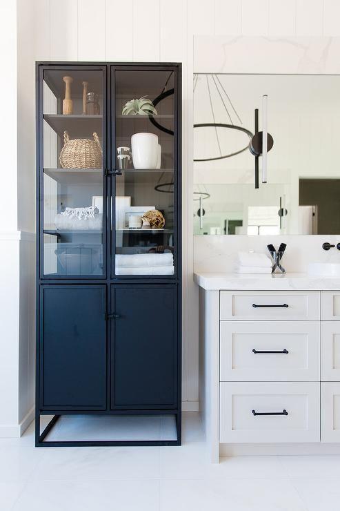 A Freestanding Black Metal Linen Cabinet With Glass Doors Is