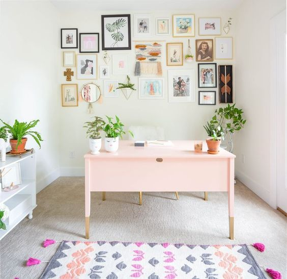 girly pink, feminine home office with large gallery wall, pink desk, west elm light and lots of plants