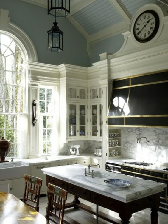 Elegant and luxurious traditional style kitchen with blue walls, white cabinetry, black work table, black range, and magnificent marble tops.