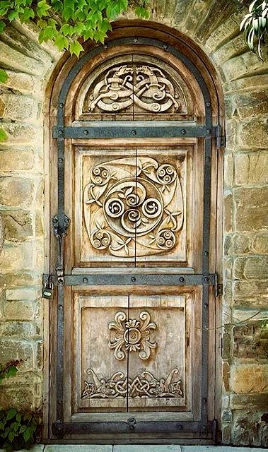 Carved wood door with arch top, wrought iron strapping set in a stone wall.