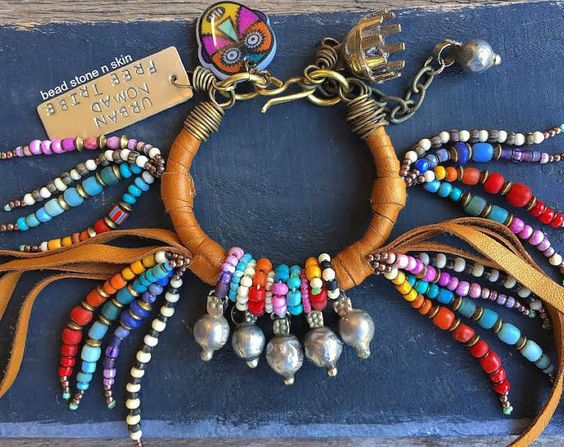 I made this eight strands rustic bracelet with trade beads, seed beads, African vintage beads, Bone beads, brass spacers, an India Bell, Vintage African chevron beads, a tassel stick, a sterling silver tag hand stamped with the words LUCKY KARMA, a large millefiori bead, an evil eye handmade by me and Kuchi charms. The brass hook clasp is handmade. The bracelet is adjustable to fit most wrists.