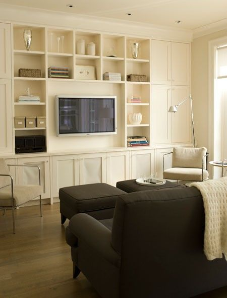 Camouflage television.   Even if the screen is at the center of wall units, shallow shelves the more integrated into the whole. Wall color fits perfectly with the shelf to create a uniform look.   Photographer:  Monic Richard  Source:  House & Home June 2010  Products:  ceramic tray, candlesticks, IKEA, glasses, glass vases mercurisé Moutarde Décor, boxes, baskets, ceramic vase, HomeSense. Design:  René Desjardins