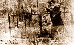 Fourteen years after Wild Bill Hickok's death, in 1900, an aging Calamity Jane arranged to be photographed next to his overgrown burial site. Elderly, thin and poor, her clothes were ragged and held together with safety pins.  Holding a flower in her hand, she said that when she died she wanted to be buried next to the man she loved. Three years later, she was.