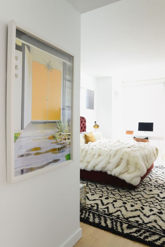 The entrance to the bedroom gets a tidy dose of color thanks to a pastel-hued framed print.