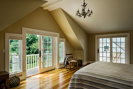 Maine Oceanfront cottage master bedroom with access to balcony and roof deck; cathedral ceiling; vintage chandelier
