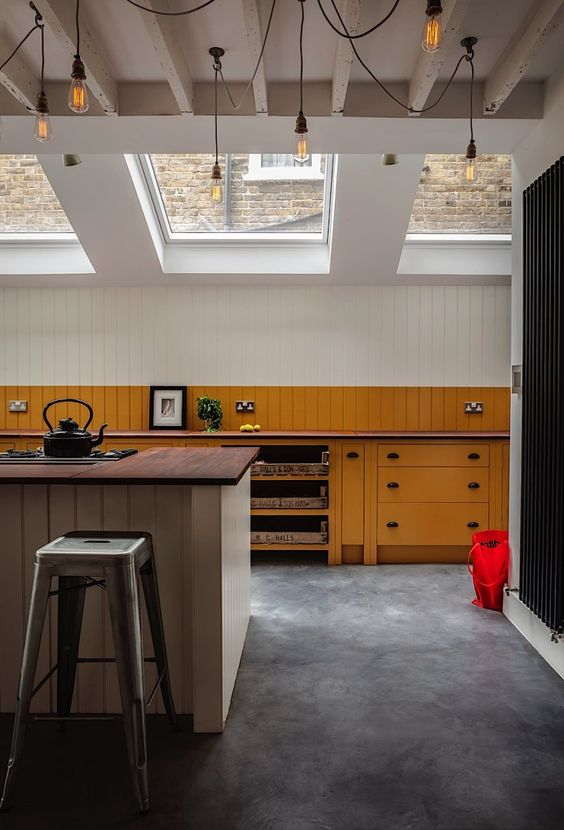 Ochre painted kitchen cabinets on polished concrete floor with fifty hanging bulbs in ceiling, British Standard Cupboards, Toni Halliday, Rachel Aspland | Remodelista