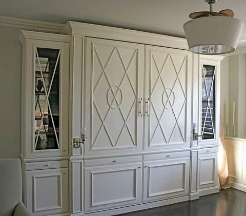 Pull out Murphy bed disguised by classy wainscoating. This wou D look nice in a library/office/formal living room. Good way to have room for company without having to have hardly ever used spare bdrooms