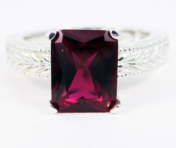 This handcrafted ring is made with a lab created ruby on a sterling silver band. The ruby is a 9x7mm emerald cut stone and is set into a 4-prong band