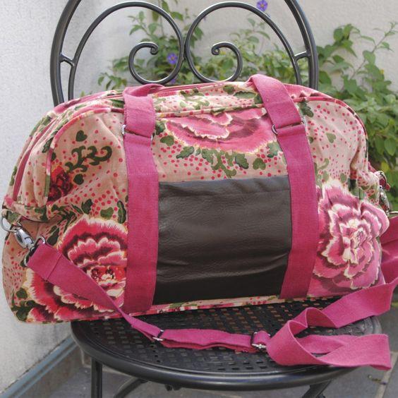Bolsa de viaje de terciopelo con dos colores en rosa y en verde azulado. Tiene un bolsillo de piel y en la parte inferior de la bolsa también va forrado con piel.