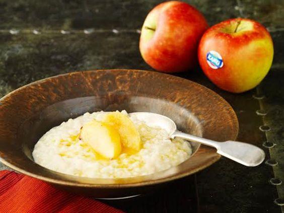 La ricetta del budino riso e mele  Per le mele: 4 mele Kanzi®, pelate e senza torsolo, tagliate in 8 spicchi, 25g di burro, 1 cucchiaio di zucchero bruno, 1 cucchiaino di cannella, 2 chiodi di garofano, 1 baccello di cardamomo, 1 baccello di vaniglia, inciso a metà. Scorza e succo di 2 arancePer il budino di riso: 20g di burro, 90g di budino di riso, 50g di zucchero semolato, 1 litro di latte parzialmente scremato, 1 cucchiaino di estratto di vaniglia, una grattata di noce moscata