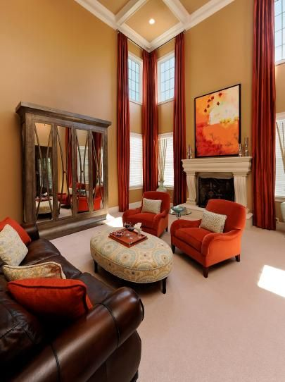 High ceiling in living room with orange chairs and brown leather sofa decorating ideas - Brown and orange living room ...
