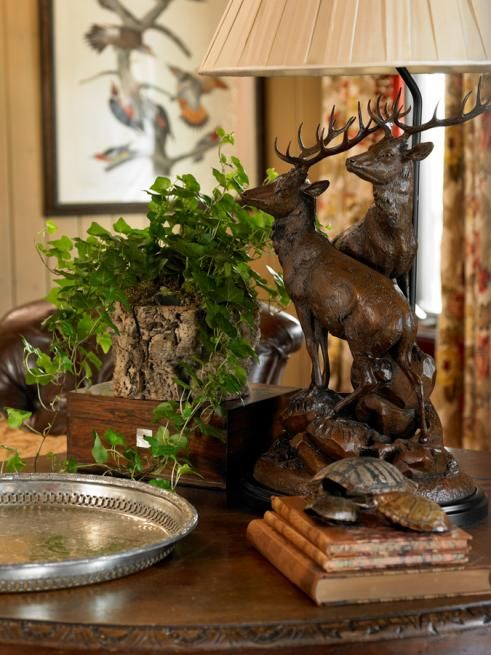 A table top with stacked books, bronze reindeer with rack table lamp, Brown and bronze