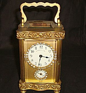 Schumann's Son Carriage Clock with alarm in working order. Gilded brass finish with beveled glass enclosure, with door in back. Beautiful trim workmanship.