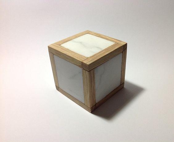 Escultura. Cubo de marmol blanco y estructura de madera.