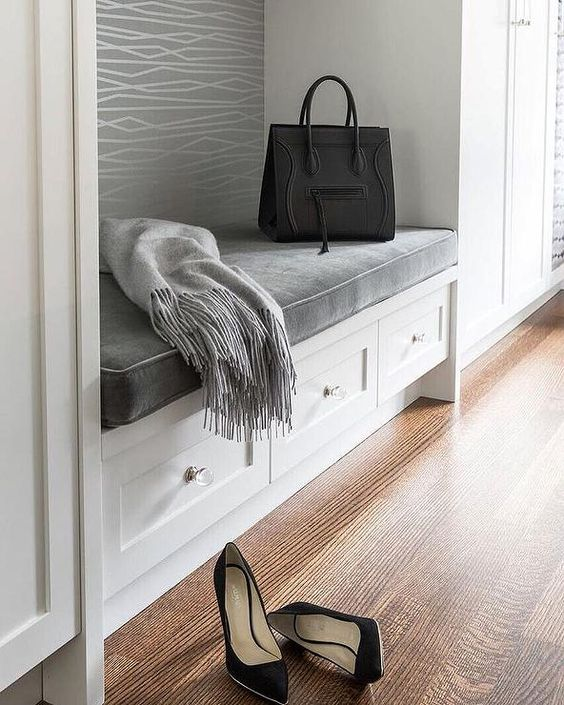 Chic white and gray mudroom features a built-in bench lined with a gray velvet seat cushion flanked by floor to ceiling cabinets.: