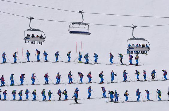 Voluntários arrumam a pista de neve antes de prova de esqui. Foto: Dimitar Dilkoff/AFP