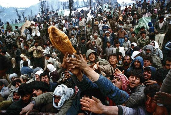 Yannis Behrakis / Reuters Frantic Kurdish refugees struggle for a loaf of bread during a humanitarian aid distribution at the Iraqi-Turkish border on April 5, 1992.
