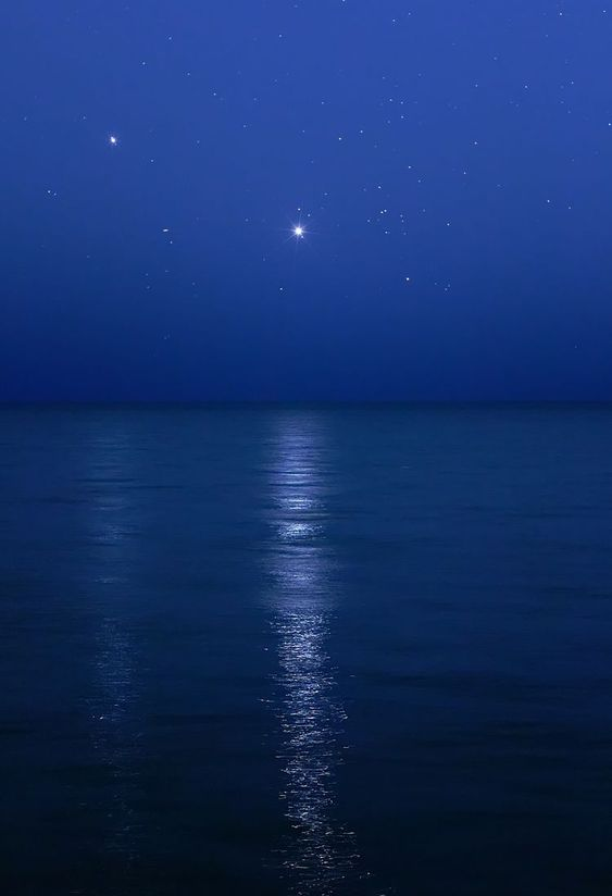 Planets Venus and Jupiter creating a glitter trail over the water.: