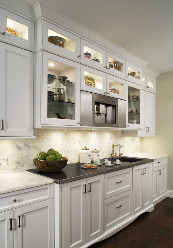 The recessed lighting illuminates this cabinetry, turning storage space into a display case. By Millennium Cabinetry & Renovations, Michigan.
