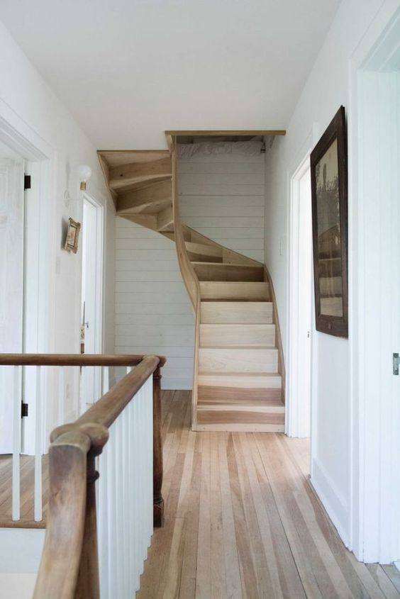 Raw wood flooring and sculptural staircase in country house by Leanne Ford with white walls and paneling. #LeanneFord #naturalwood #staircase